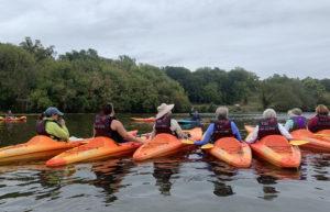 Women in orange kayaks on the river
