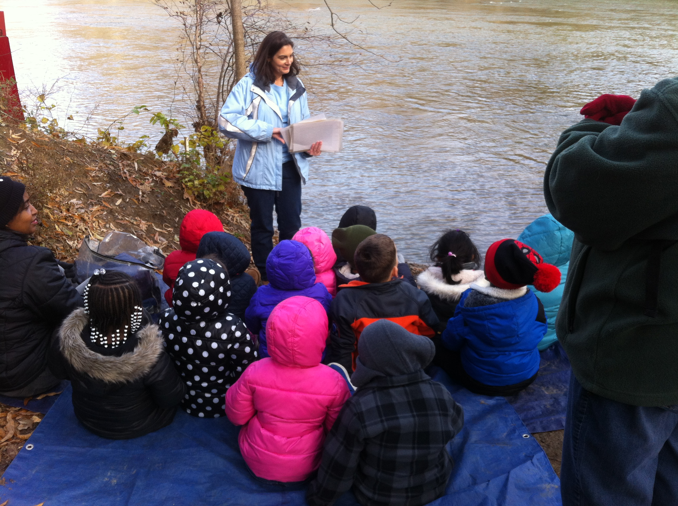 children listen to teacher by river