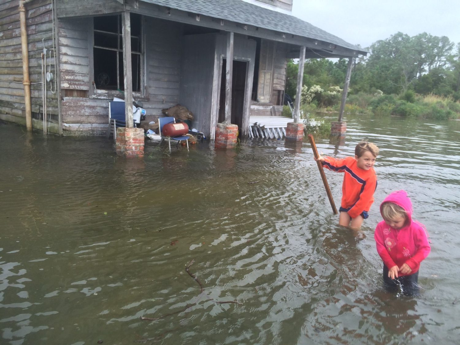 children wage in waist high water in front of flooded house