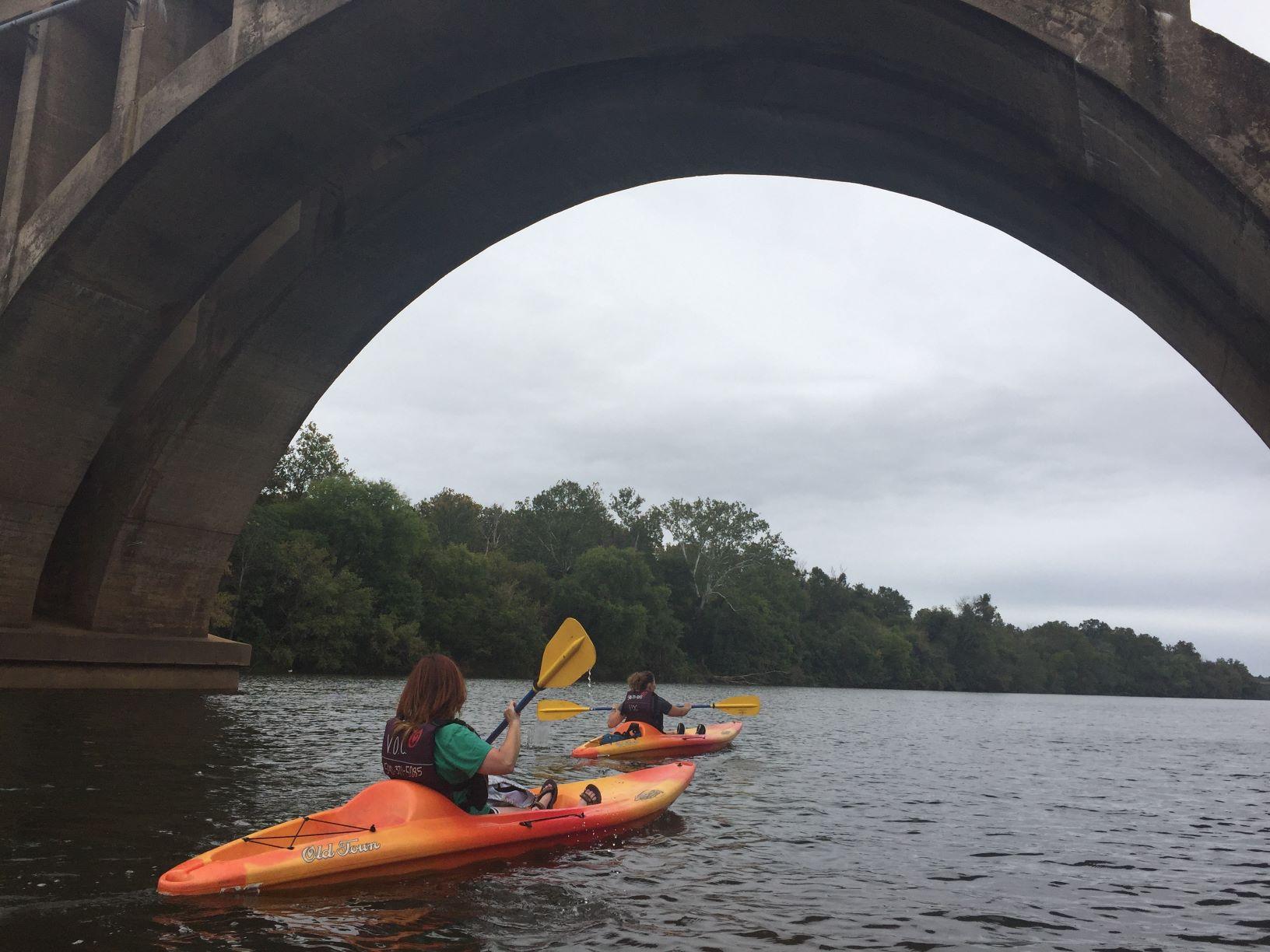 Women kayaking under bridge