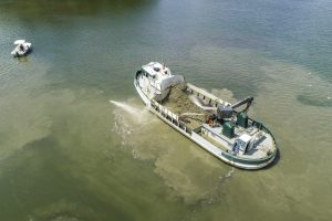 large boat spraying oyster shell into river
