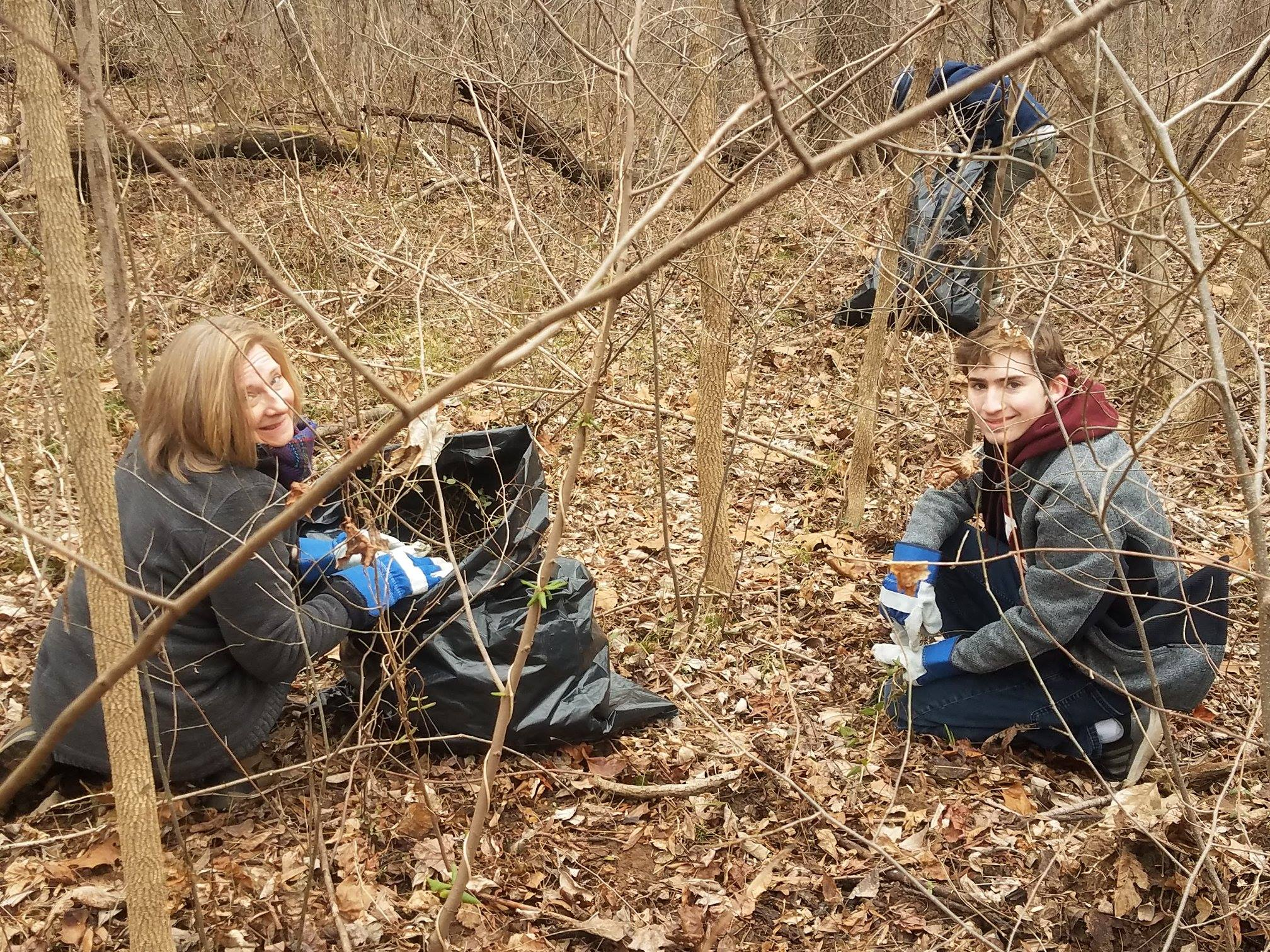 volunteers kneeling in woods with trashbags