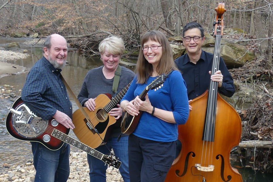 Four people with instruments standing in a creek